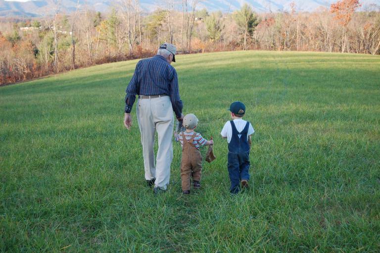 Older farmer walking with children through field