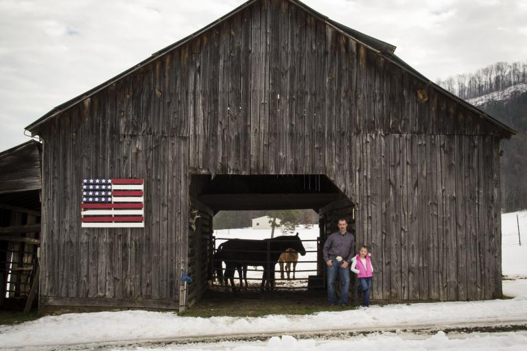 Father and daughter posing by barn